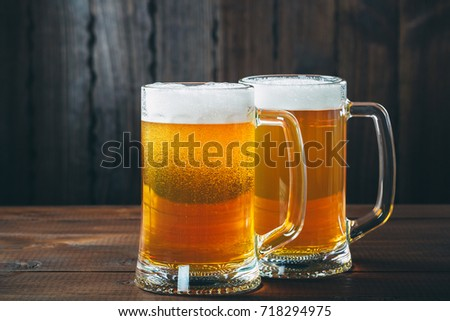Two Mug of beer on the wooden background. Beautiful background of the Oktoberfest