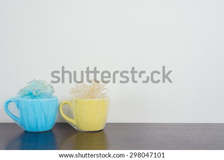 Two mug on wooden table over grunge background. Colorful stack coffee cups on wood board. Vintage retro effect style pictures. - stock photo