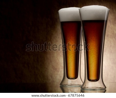 two mugs of beer against a stone wall - stock photo