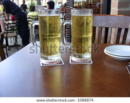 Two mugs of beer served at outdoor restaurant. - stock photo