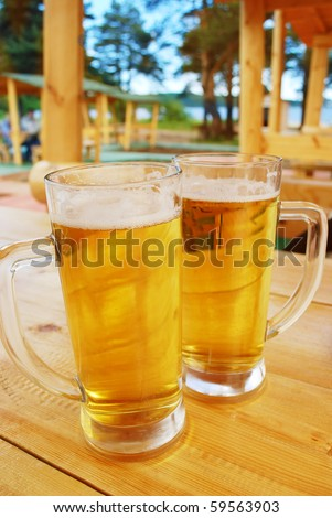 Two mugs of beer staying on the wood table in outside bar. - stock photo