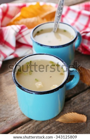 Two mugs of soup and napkin on wooden background