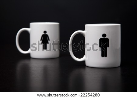 Two mugs, one man standing (focused) in front of the woman, isolated on a black background. - stock photo