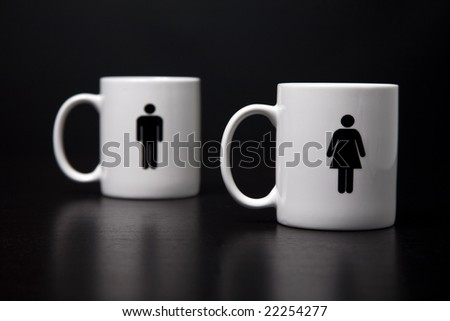 Two mugs, one woman standing (focused) in front of the man, isolated on a black background. - stock photo