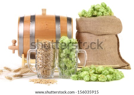 Two mugs with barley and hop. Isolated on a white background. - stock photo