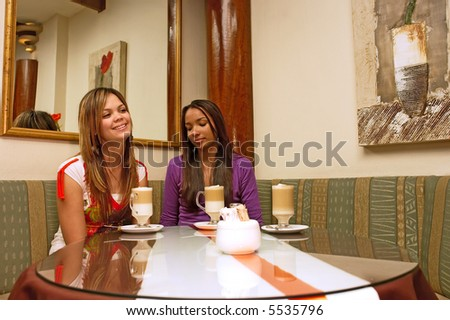 Two mulatto girls sit in a cafe with mirrors. Shot in Western Cape, South Africa.