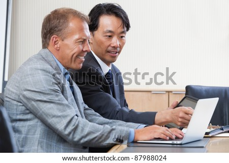 Two multi-ethnic colleagues working together on a computer - stock photo