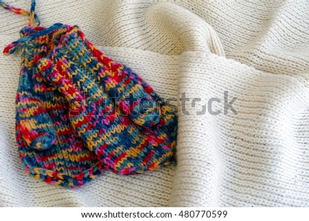 Two multicolored knitted mittens on a white scarf
