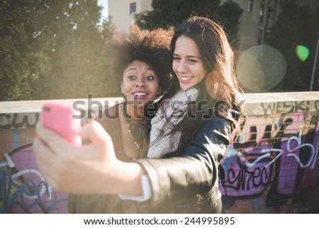 two multiethnic beautiful young woman black and caucasian having fun taking selfie in town - stock photo