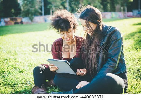 two multiethnic beautiful young woman black and caucasian using tablet sitting in a city park, looking down the screen smiling - technology, social network, happiness concept - stock photo