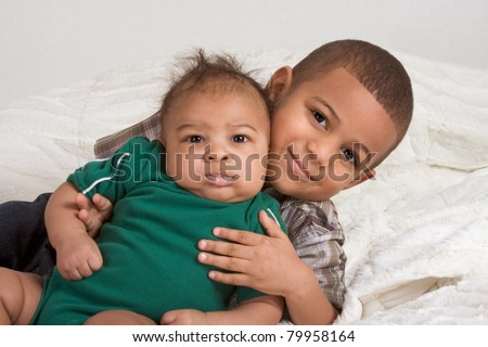 Two multiethnic boys brothers of mixed race one 3 months old and another 3 years - stock photo