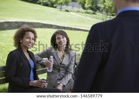 Two multiethnic businesswomen on park bench looking at businessman