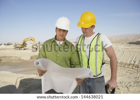 Two multiethnic construction workers reading blueprints at site - stock photo