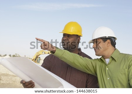 Two multiethnic construction workers with blueprints against the sky at site - stock photo