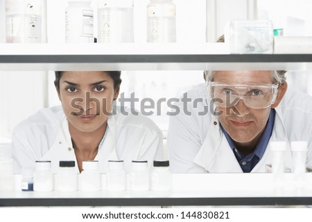 Two multiethnic scientists looking through shelves in laboratory