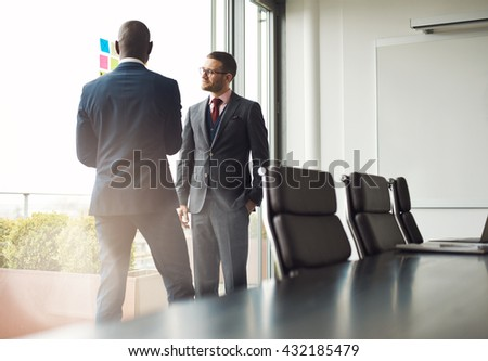 Two multiracial businessmen standing talking together in front of a window in a conference room, view over the table with sun flare through the window - stock photo