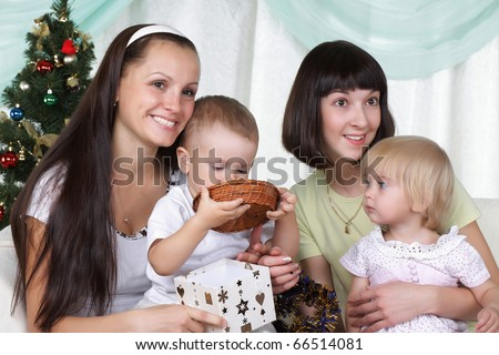 Two mums and their kids sits near a christmas fur-tree - stock photo