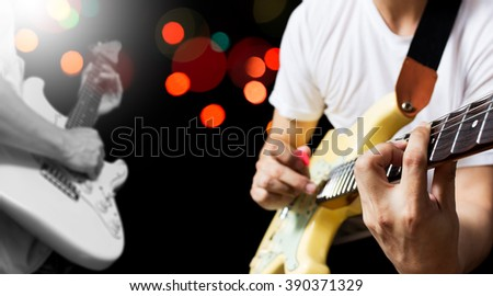 two musician playing and jamming guitar with colourful bokeh on stage in concert for music contest concept background - stock photo