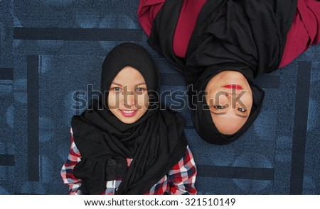 Two muslim girls lying side by side.    - stock photo