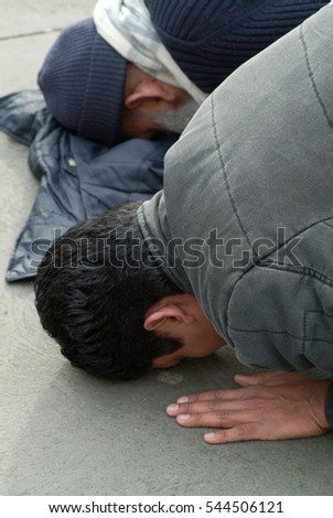 Two Muslim men praying in public, during protest against Israeli aggression in Gaza in Trafalgar square, London, 11/02/2006
