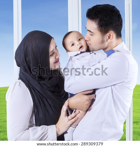 Two muslim parents carrying and kissing their baby near the window at home - stock photo