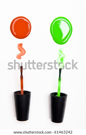 Two nail polish brushes, with green and red polish on white background - stock photo