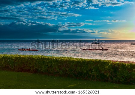 Two native Hawaiian boats rowing past at sunset on Maui, Hawaii, USA - stock photo
