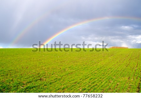 two natural rainbow over green field - stock photo