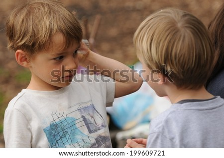 Two naughty boys playing in the forest - stock photo