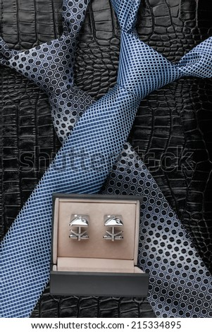 Two necktie and  cufflinks  lying on the skin, can be used as background - stock photo