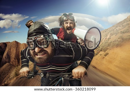 Two nerdy guys riding on a bike - stock photo