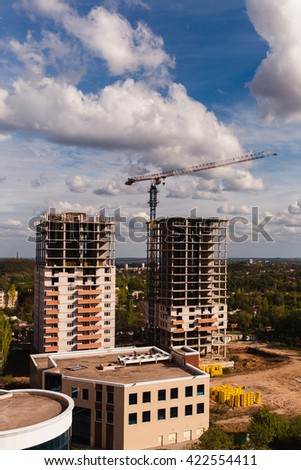 Two new building high-rise buildings against a beautiful sky with clouds. Near construction crane  - stock photo