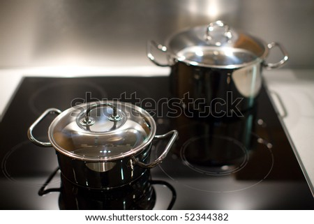 Two new stainless steel saucepans on modern kitchen range - stock photo