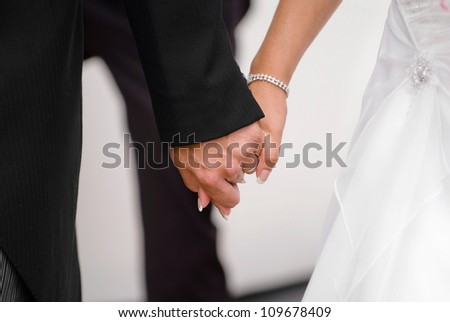 Two newly wedded lovers holding hands.