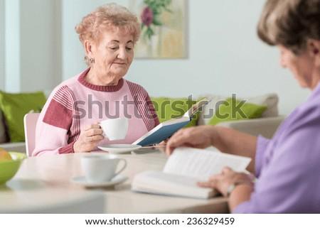 Two nice elderly women reading books in living room - stock photo