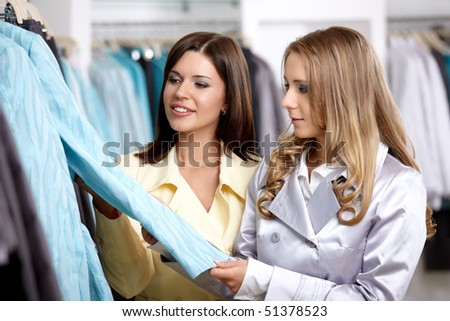 Two nice girls consider clothes in shop - stock photo