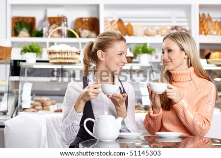Two nice girls drink tea in cafe - stock photo