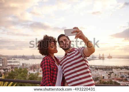 Two nice young people taking a selfie while standing on a bridge that overlooks a city with bright clouds behind them