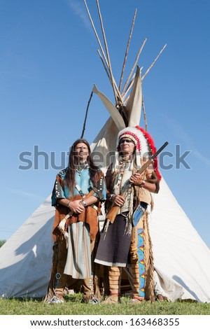 Two North American Indians stand near a wigwam - stock photo