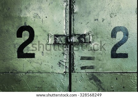 Two number twos on a dirty industrial wall. - stock photo