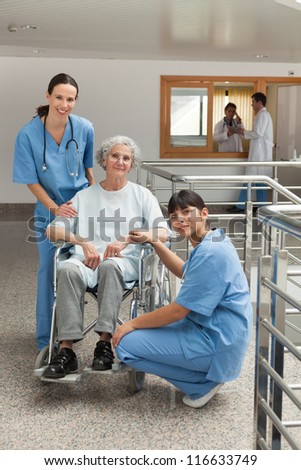 Two nursed with old woman in wheelchair in hospital corridor - stock photo