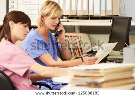 Two Nurses Working At Nurses Station - stock photo