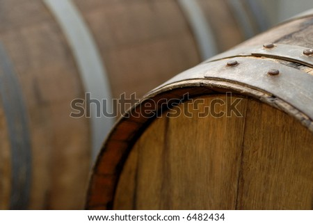 Two oak wine barrels at a winery, the one in the foreground is in focus - stock photo