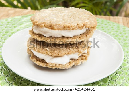 Two oatmeal cookie ice cream sandwiches on a white plate