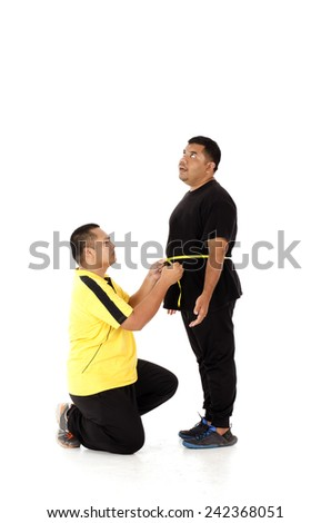 Two obesity man with big belly feeling shock measuring their size - stock photo
