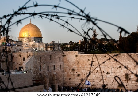 Two of Islam and Judaism's holiest sites, Jerusalem's Dome of the Rock and the Western Wall, seen through barbed wire. - stock photo