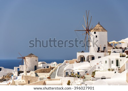 Two of the traditional windmills of Oia on the greek paradise island of Santorini. - stock photo