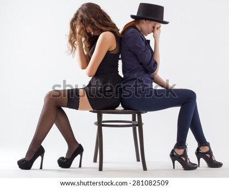 Two offended young women sitting on a chair back to back.