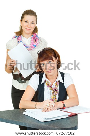 Two office girls looking at you over a laptop - stock photo