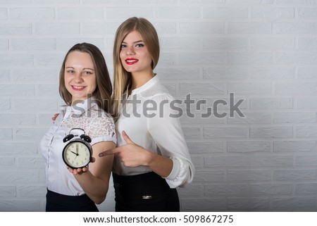 Two office worker with a clock and a folder on a background of white brick wall